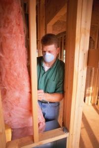 Man installing fiberglass insulation