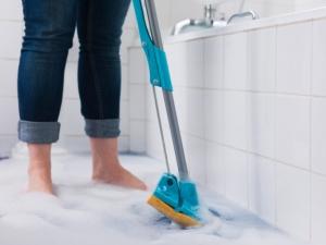 Woman cleaning overflowing bathtub